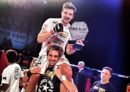 Bruno e carregado nos ombros por seu irmão e parceiro de banda Kiko após a vitória na estreia no MMA