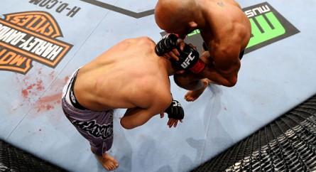 Na posição de John Dodson (bermuda cinza) acima, um lutador poderá ser golpeado na cabeça mesmo se tocar o chão com uma mão. Foto: Josh Hedges/UFC.com