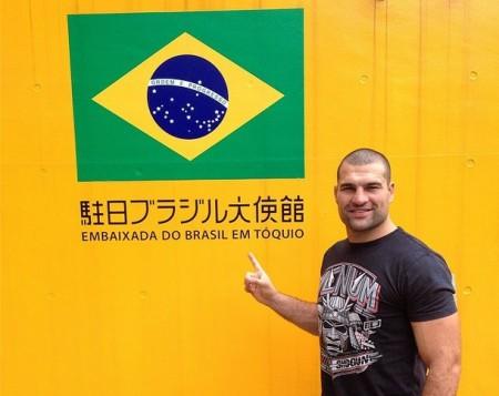 M. Shogun posa ao lado da bandeira brasileira na embaixada em Tóquio. Foto: Reprodução/Instagram