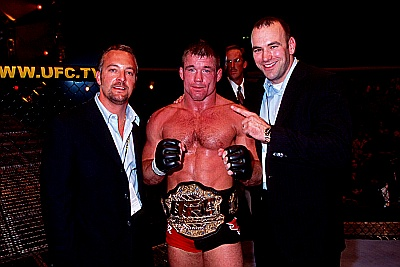 M. Hughes (centro) recebe o cinturão de Dana White e Lorenzo Fertitta. Foto: Divulgação