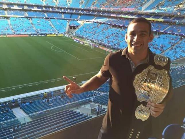 Werdum exibe o cinturão na Arena do Grêmio minutos antes do GreNal. Foto: Reprodução/Twitter